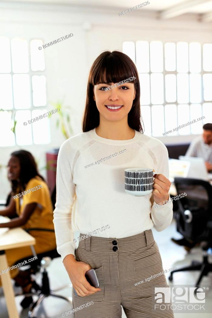 Stock Photo: Portrait of smiling young woman in office with colleagues in background.