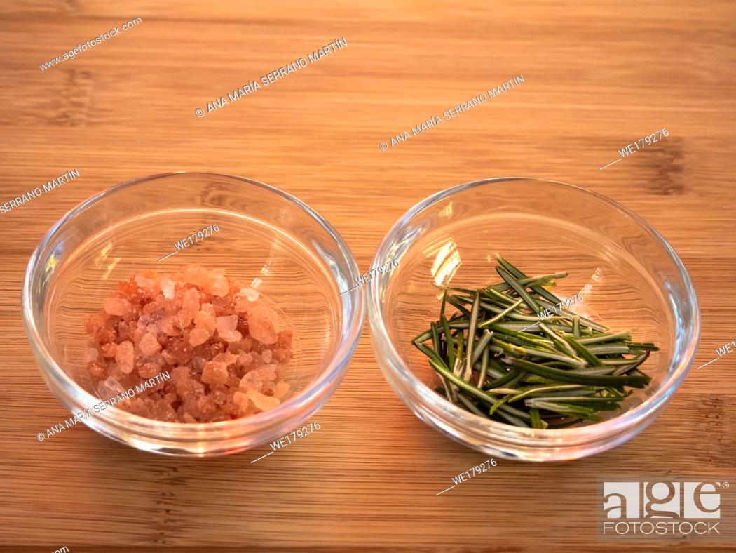 Stock Photo: Crystal bowls with himalayan pink salt and rosemary on a wooden table.