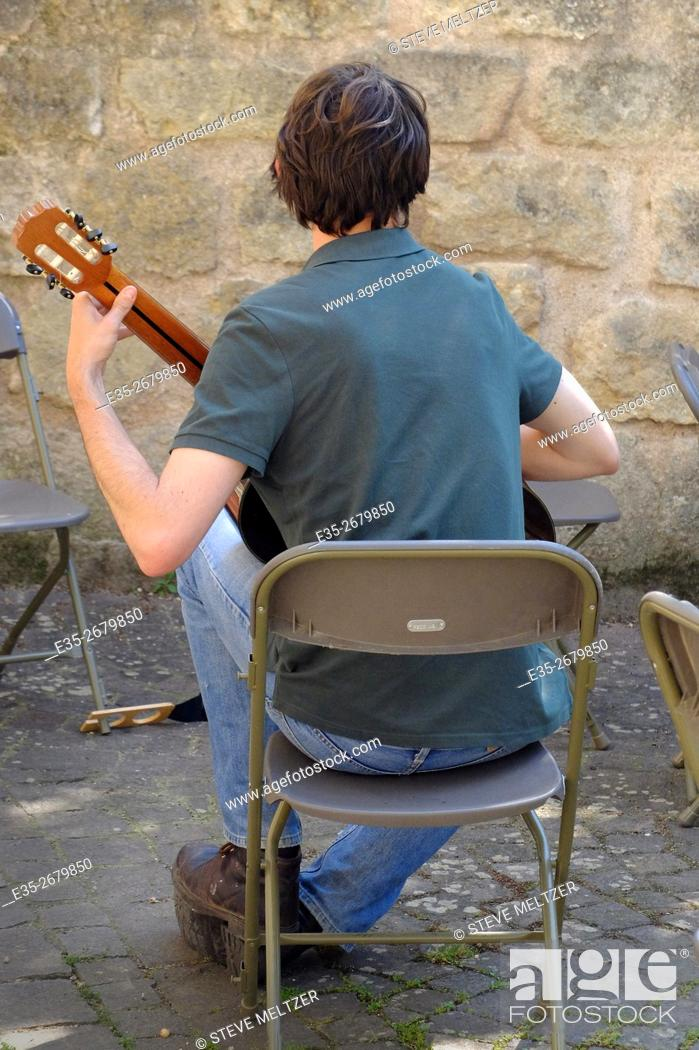 Stock Photo: Practicing guitar alone.