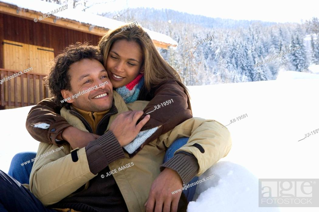 Stock Photo: Mixed race couple hugging in winter setting.