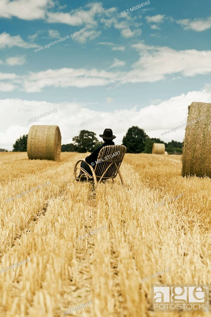 Imagen: Teenage boy with hat sitting in a rocking chair on a grainfield.