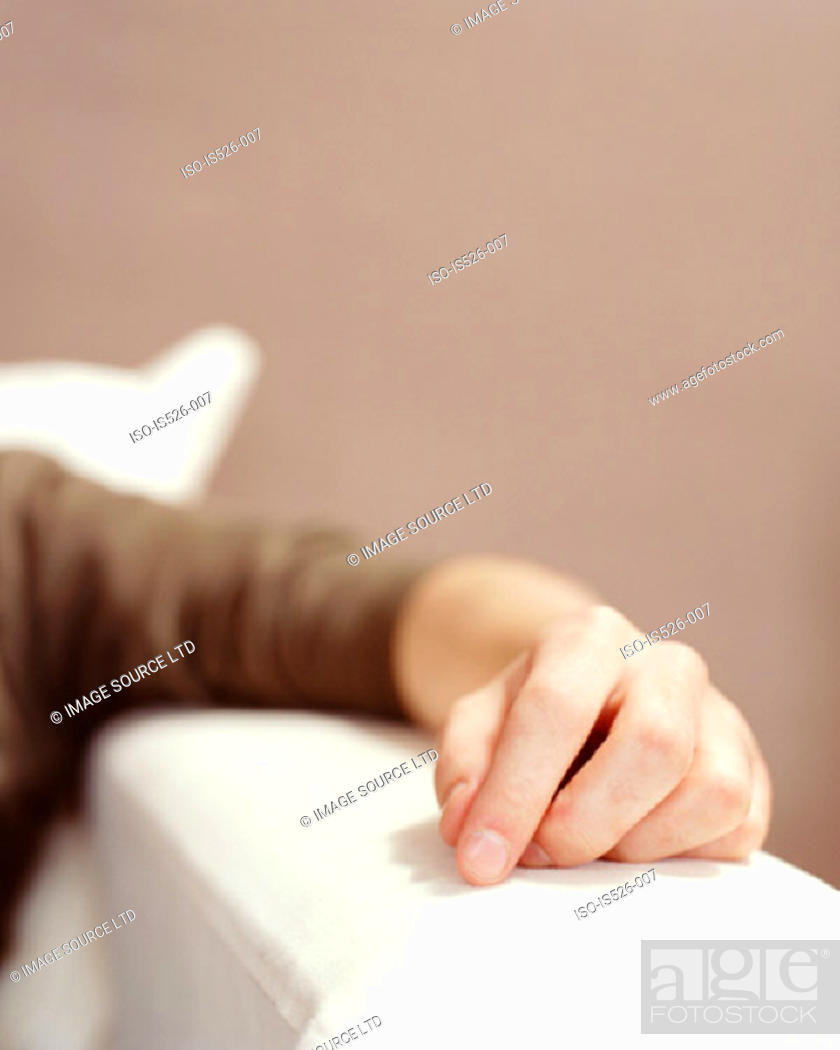 Stock Photo: A male hand on the sofa arm.