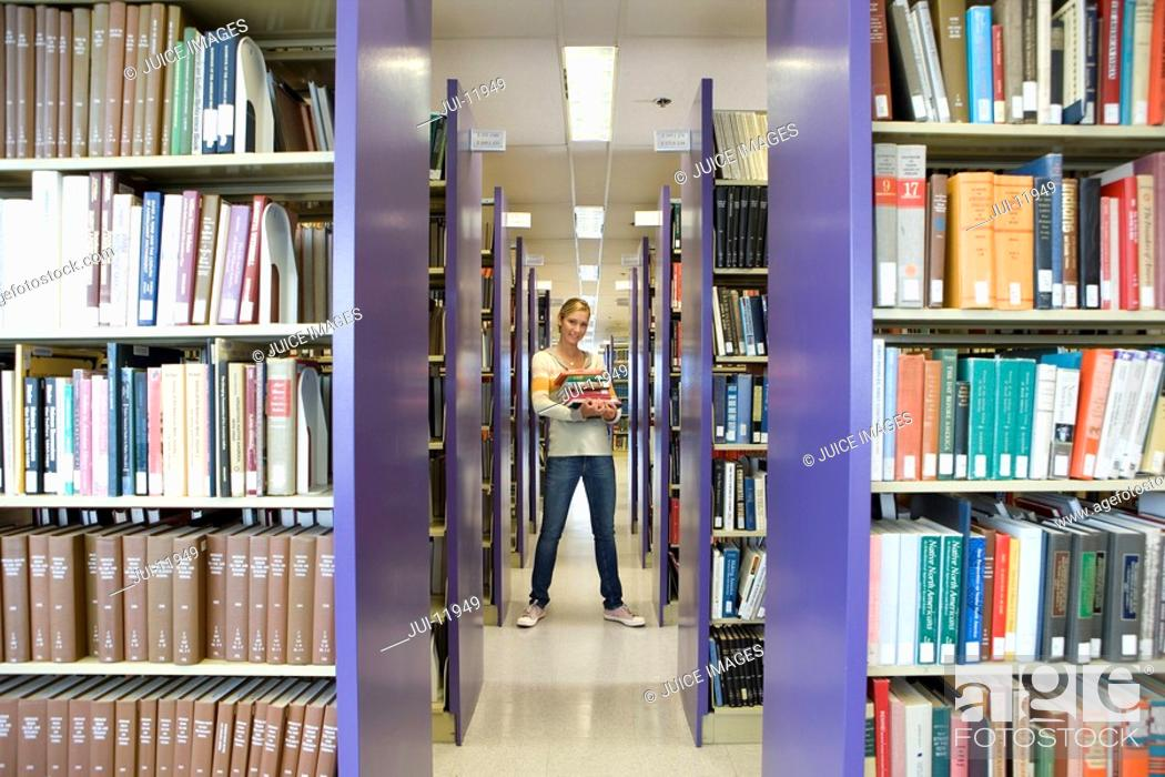 Stock Photo: Young woman with armful of books in library, smiling, portrait.