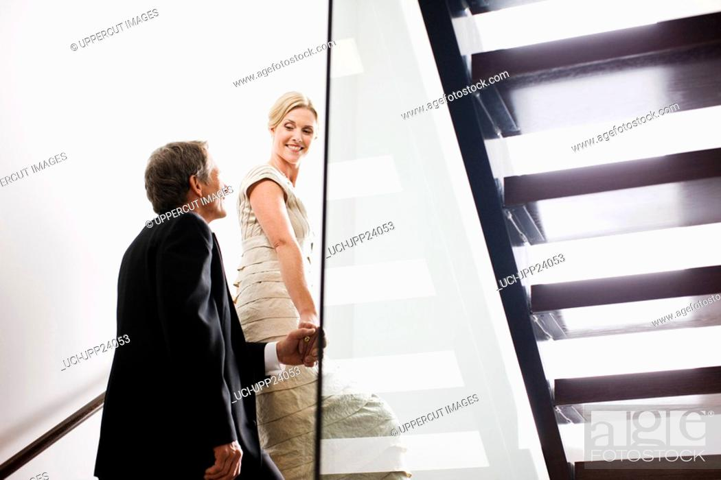 Stock Photo: Couple in eveningwear ascending staircase.
