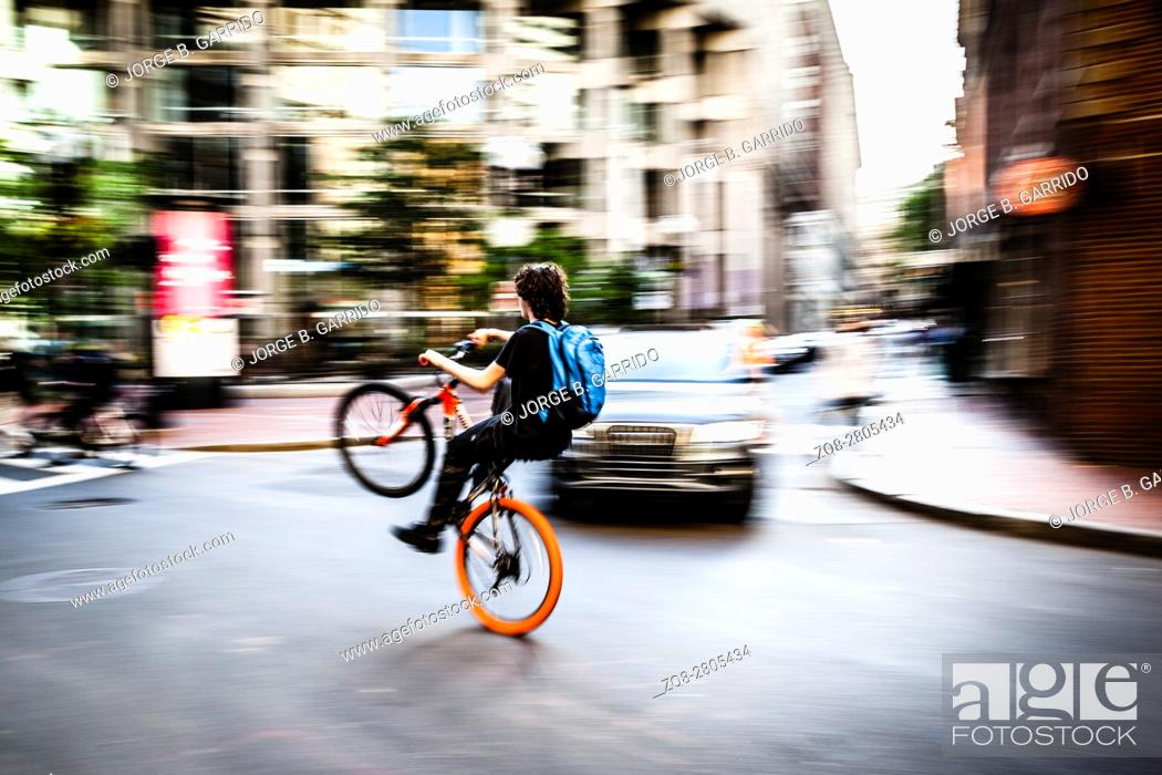 Stock Photo: American boys doing stunts on the bicycle in the streets of Boston.