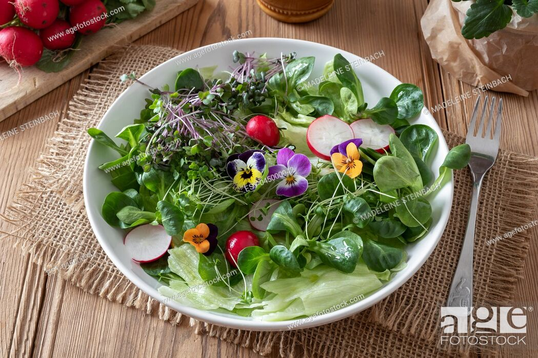 Stock Photo: Spring salad with fresh broccoli and kale microgreens and colorful edible pansy flowers.