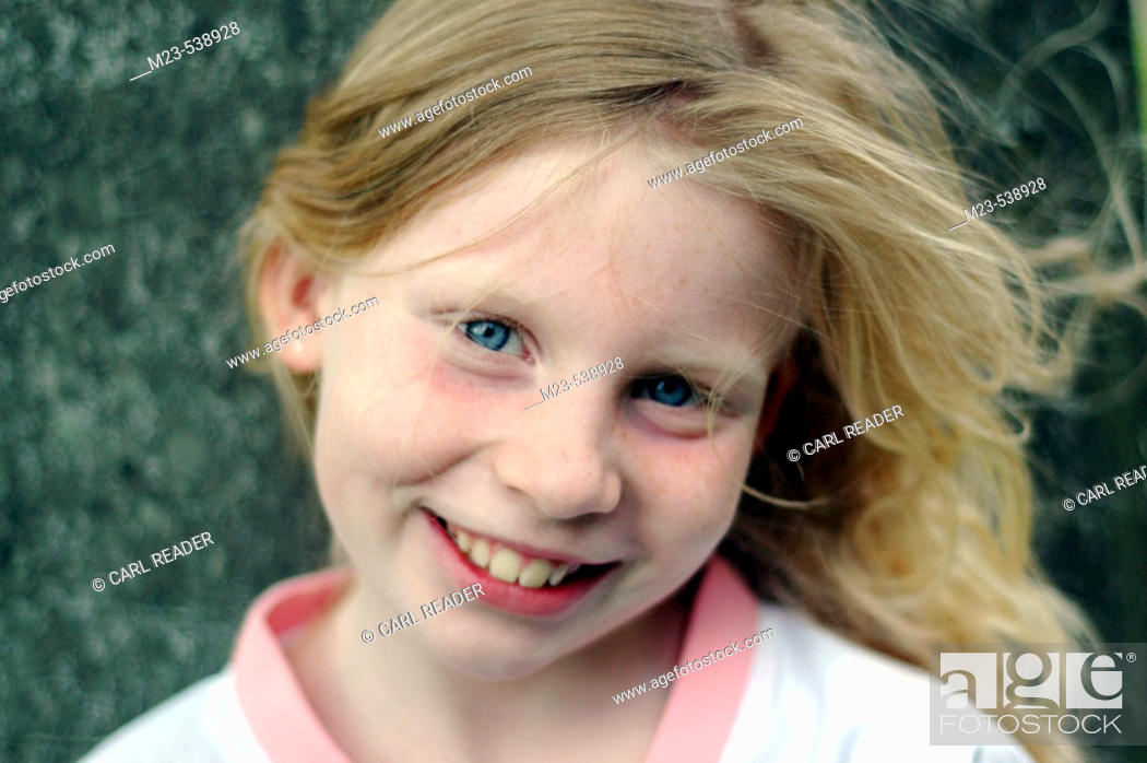 Stock Photo: A little girl gives a charming smile.