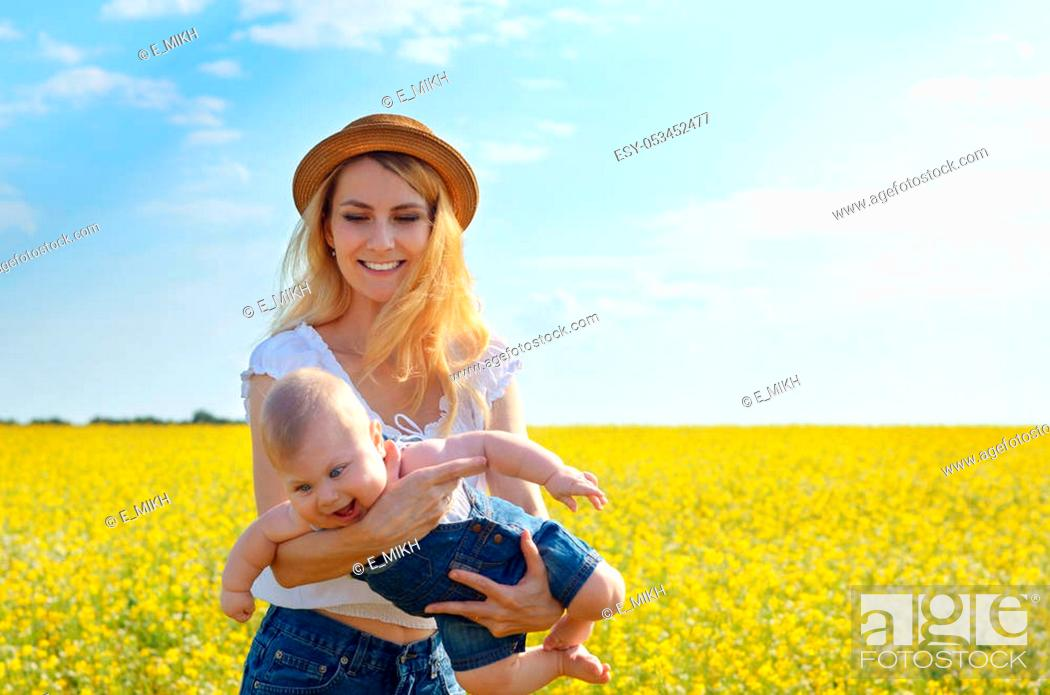 Stock Photo: Young happy mother with her infant son at canola field.