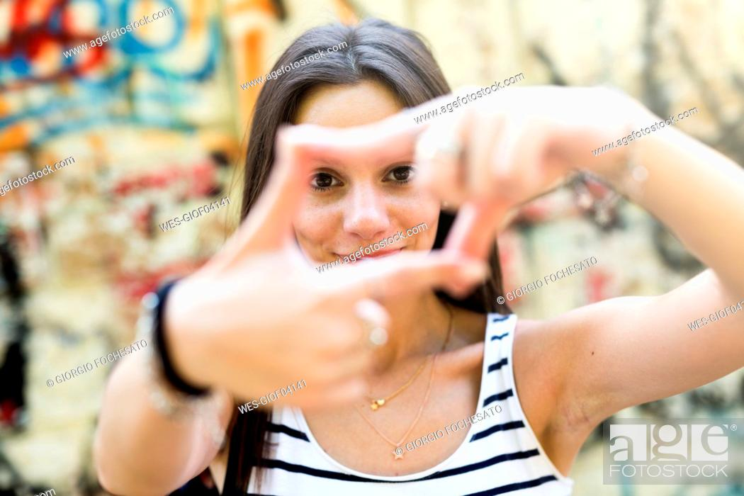 Stock Photo: Portrait of young woman shaping frame with her fingers.