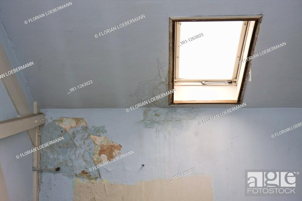 Stock Photo: An attic in need of renovation with bright roof light. The wallpaper is peeling off because of a water-damage. Shot in Aachen, Germany.