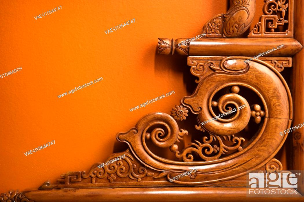 Stock Photo: Ornate wooden Asian furniture carving against orange wall.