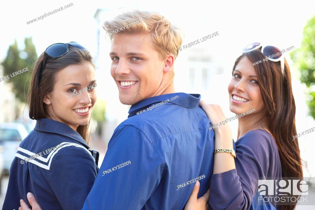 Stock Photo: Portrait of a young man with two women smiling.