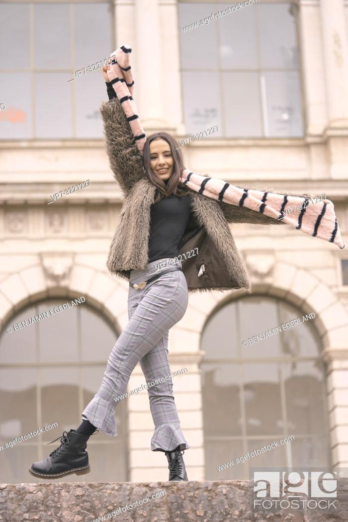 Stock Photo: playful woman in fashionable winter clothes, playing with scarf, happy, in front of wealthy historical architecture, in Munich, Germany.