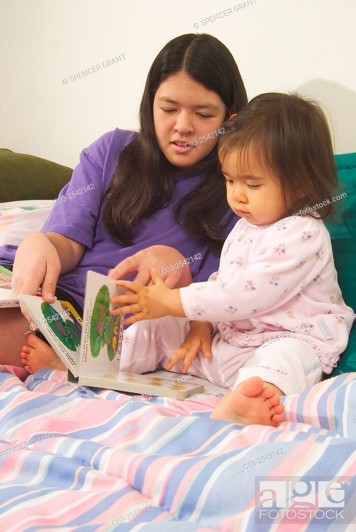 Stock Photo: An Asian American teen girl reads to her infant sister in bed while babysitting in Laguna Beach, CA. MODEL RELEASE.