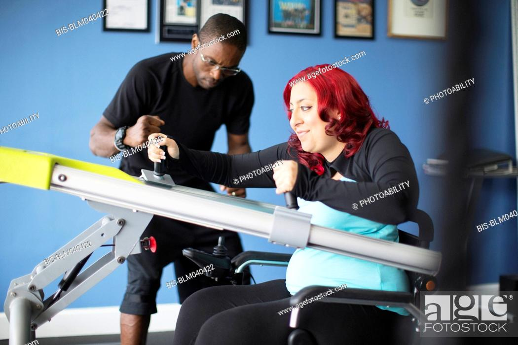 Stock Photo: Disabled woman doing physical therapy with trainer.