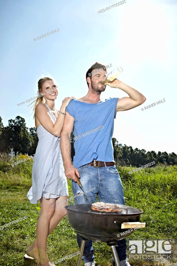 Stock Photo: Germany, Cologne, Young couple grilling sausage and drinking beer.