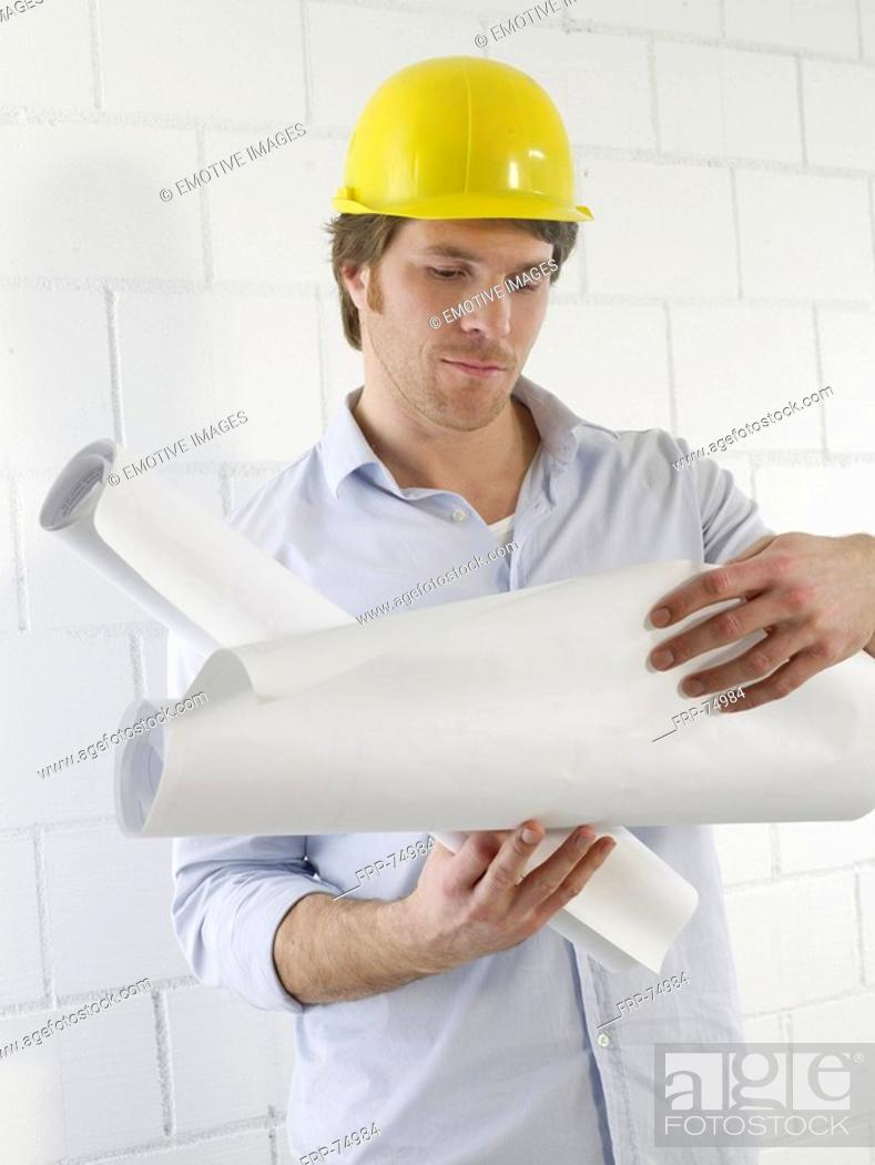 Stock Photo: Man is reading construction plans.
