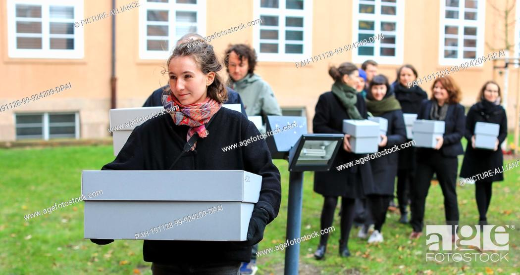 Stock Photo: 28 November 2019, Saxony, Leipzig: Museum staff carry crates containing the bones of indigenous Australians in the courtyard of the Grassi Museum as part of the.