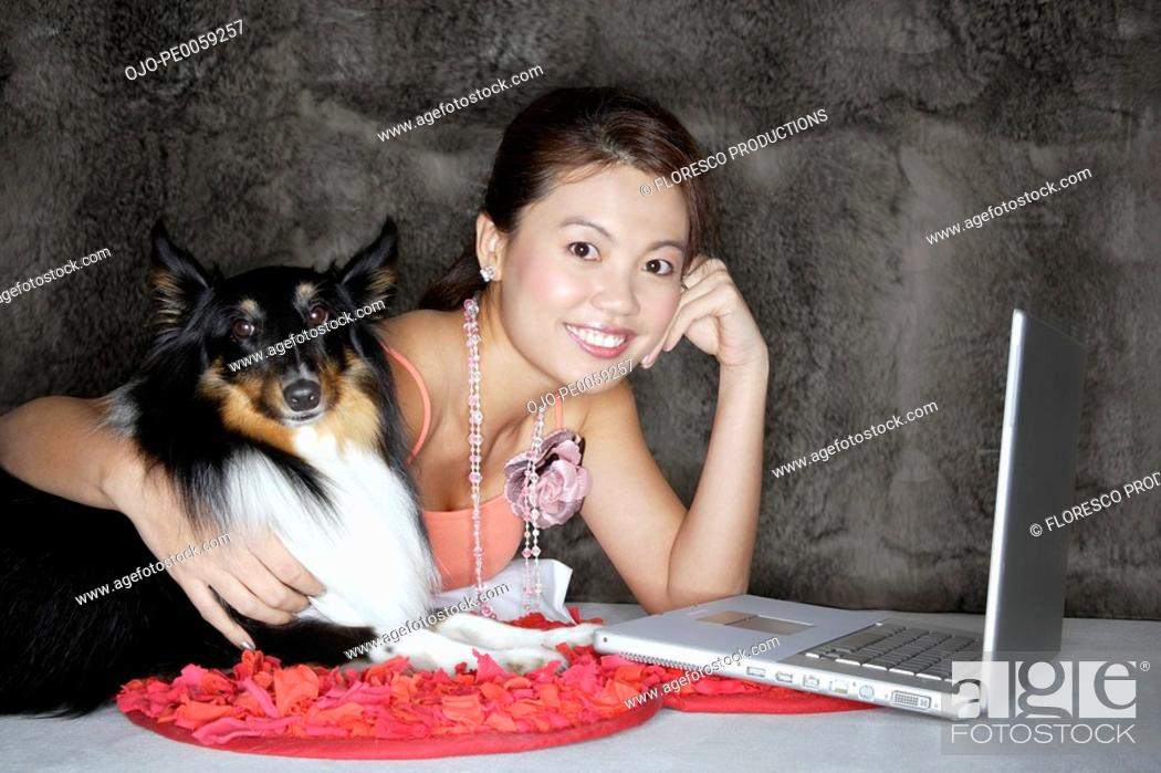 Stock Photo: Woman with dog and laptop indoors.