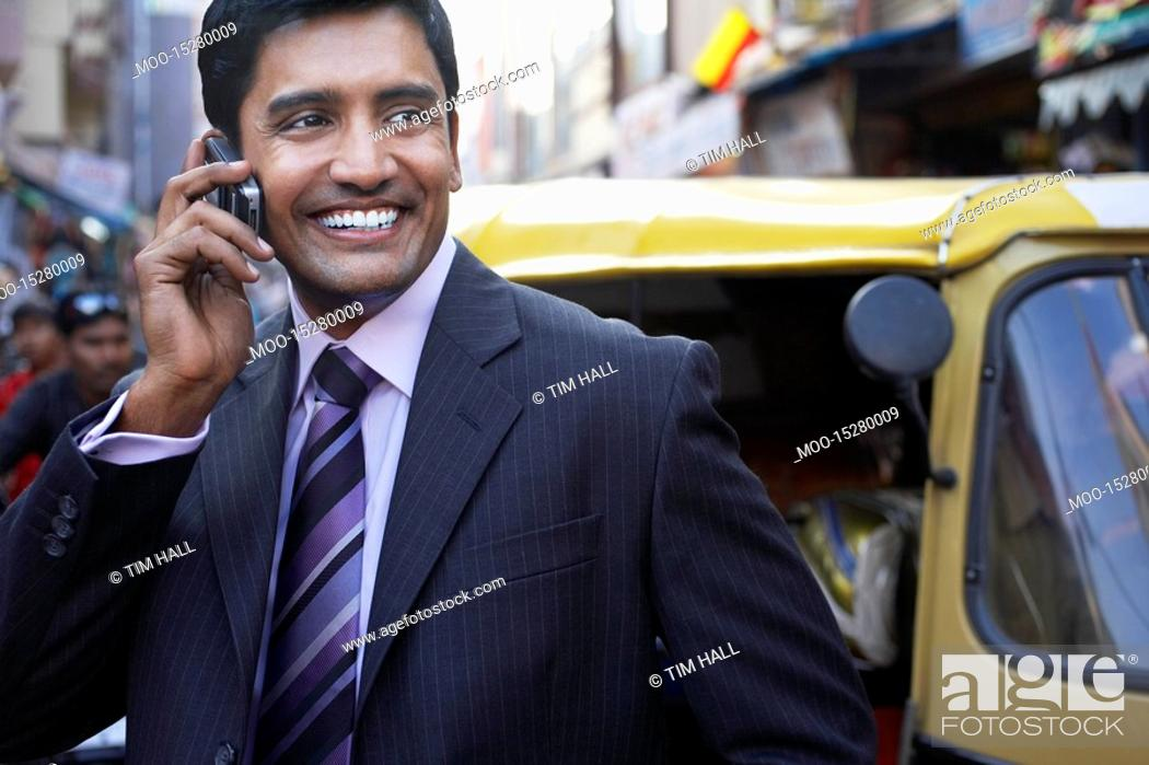 Stock Photo: Business man using cell phone smiling.