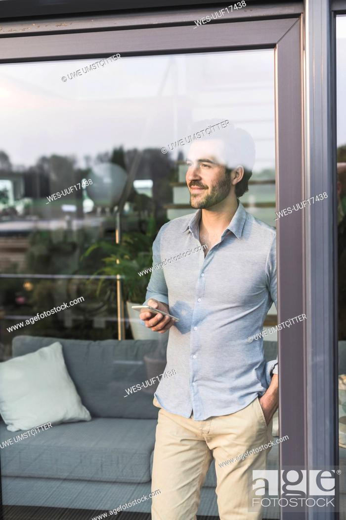 Stock Photo: Young man looking out of window, using smartphone.