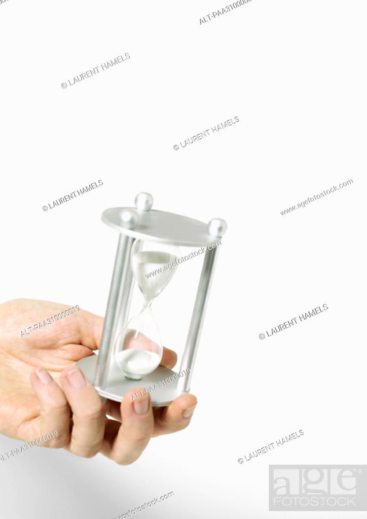 Stock Photo: Hand holding hourglass.