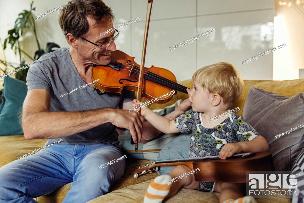 Imagen: Toddler watching his father playing violin.