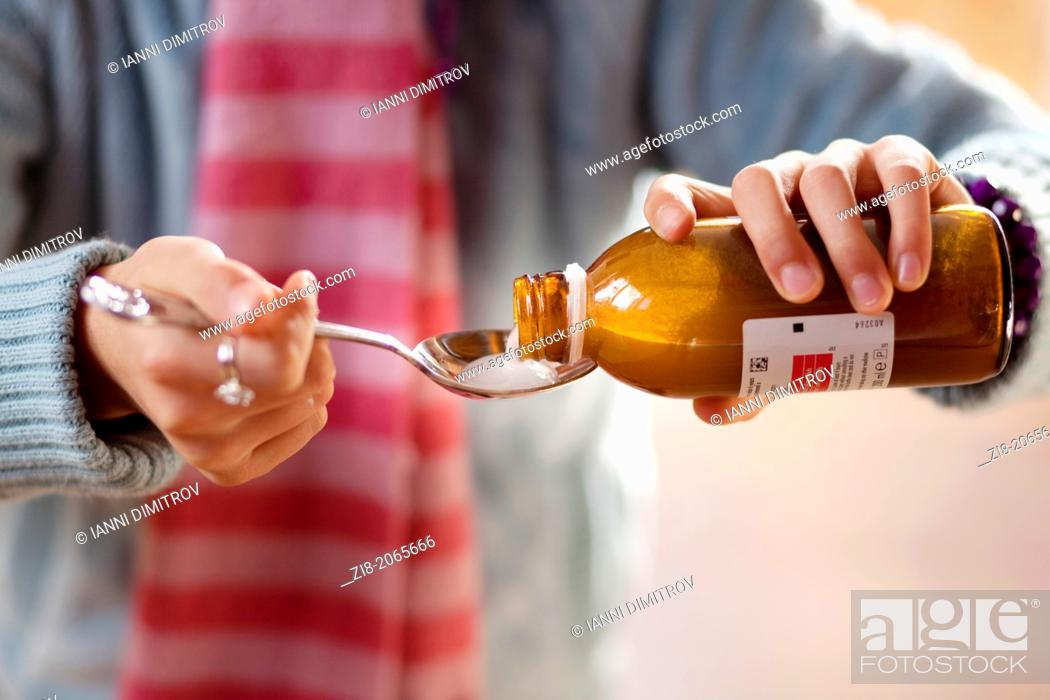 Stock Photo: Child pouring cough medicine -close-up.
