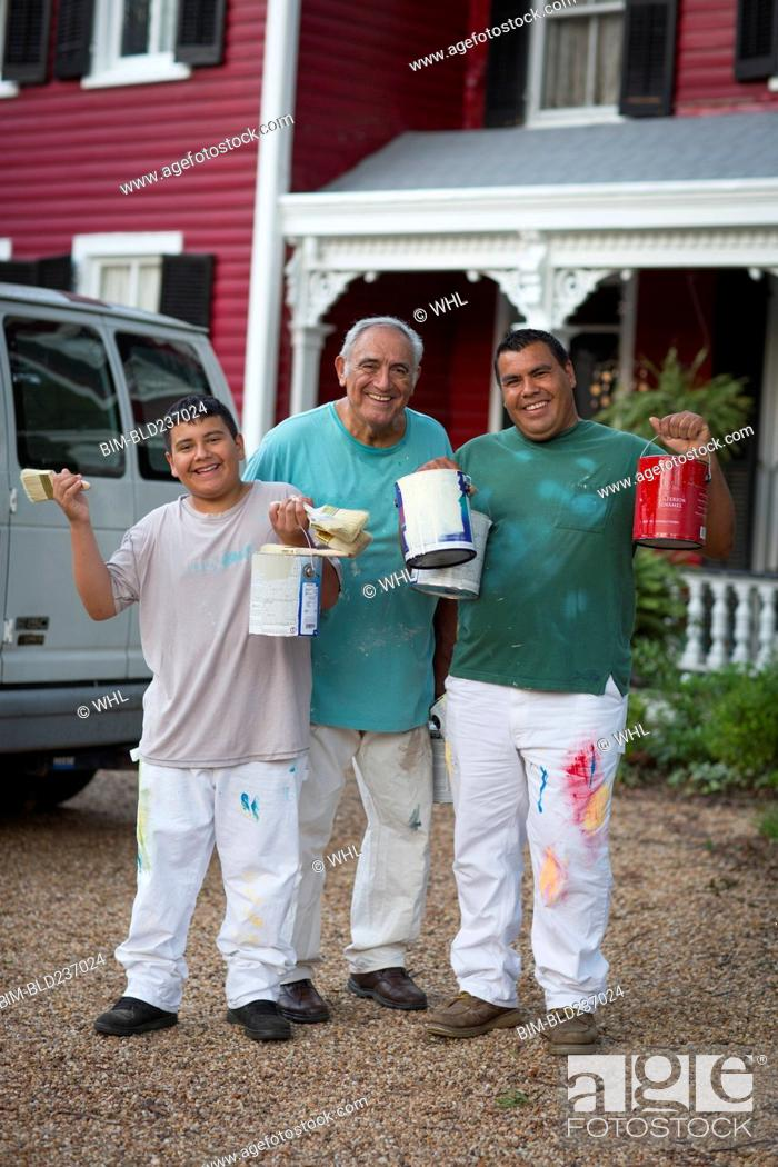 Stock Photo: Smiling Hispanic men and boy posing with paint cans and paintbrushes.
