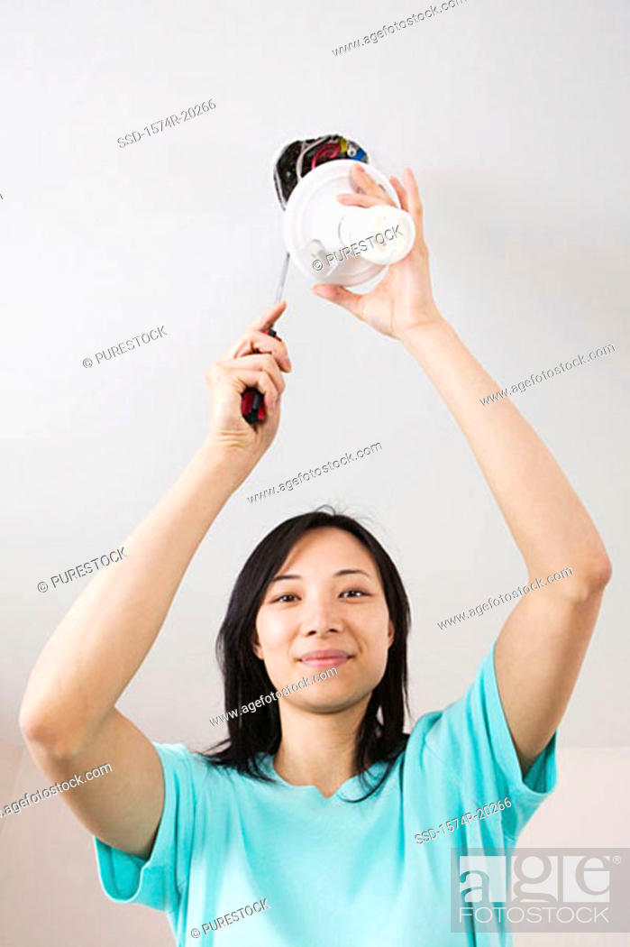 Stock Photo: Low angle view of a young woman fixing a light fixture.