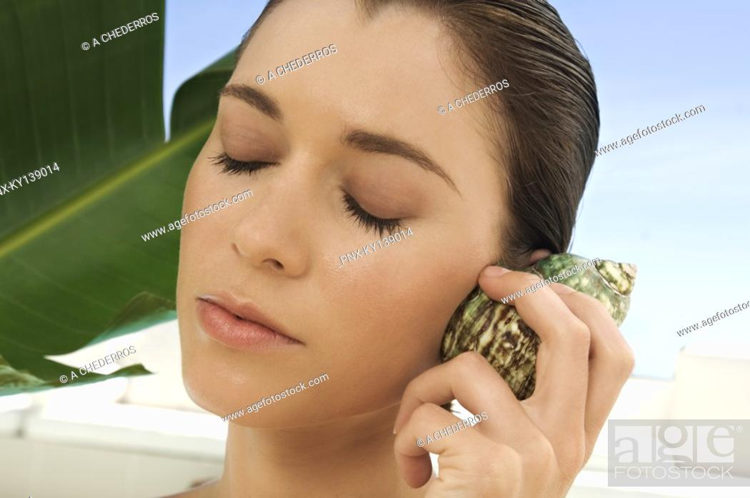 Stock Photo: Portrait of a young woman holding a shell against her ear, outdoors.