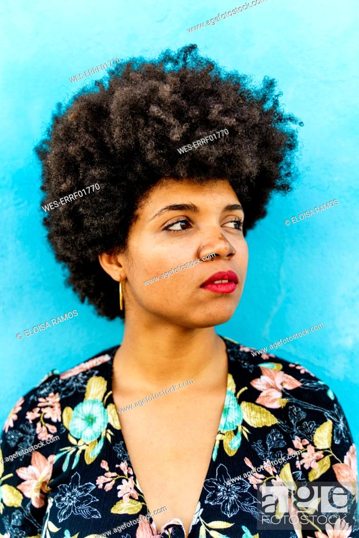 Stock Photo: Portrait of female Afro-American woman, blue wall in the background.