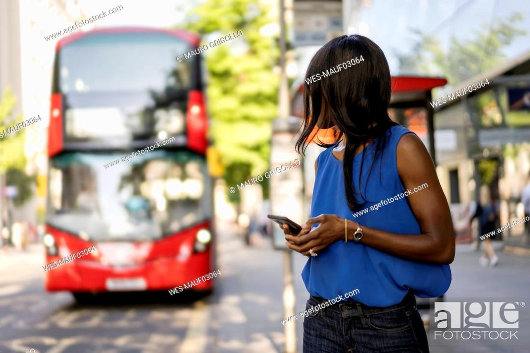 Stock Photo: Female Afro-American using smartphone at bus stop in London, United Kingdom.
