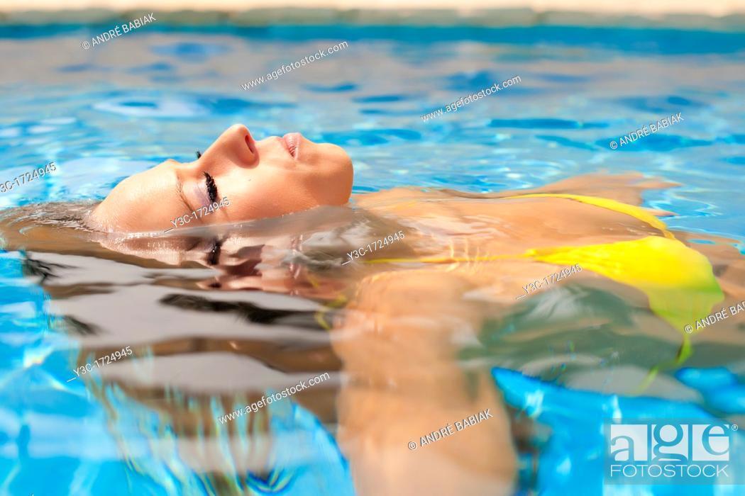 Stock Photo: Beautiful woman in bikini enjoying a bath in a swimming pool.