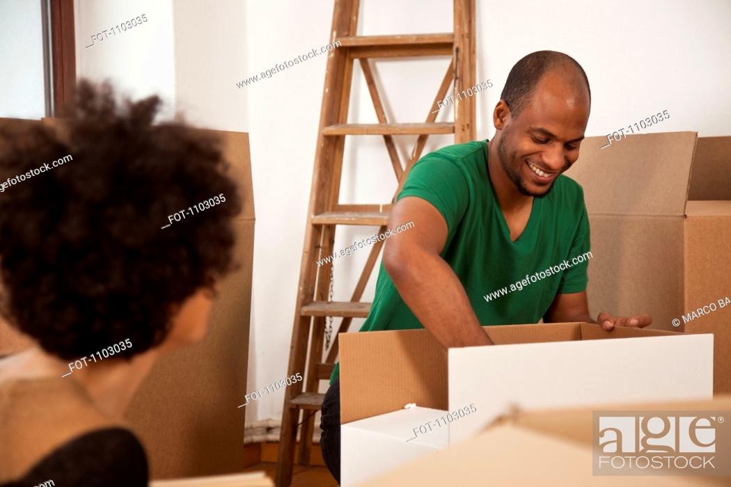 Stock Photo: A couple packing moving boxes, focus on man.