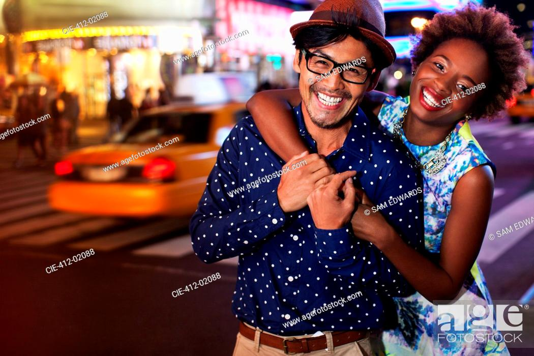 Stock Photo: Couple smiling on city street at night.