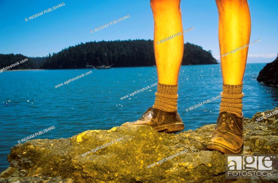 Stock Photo: Legs of Hiker on Rocks by Ocean.