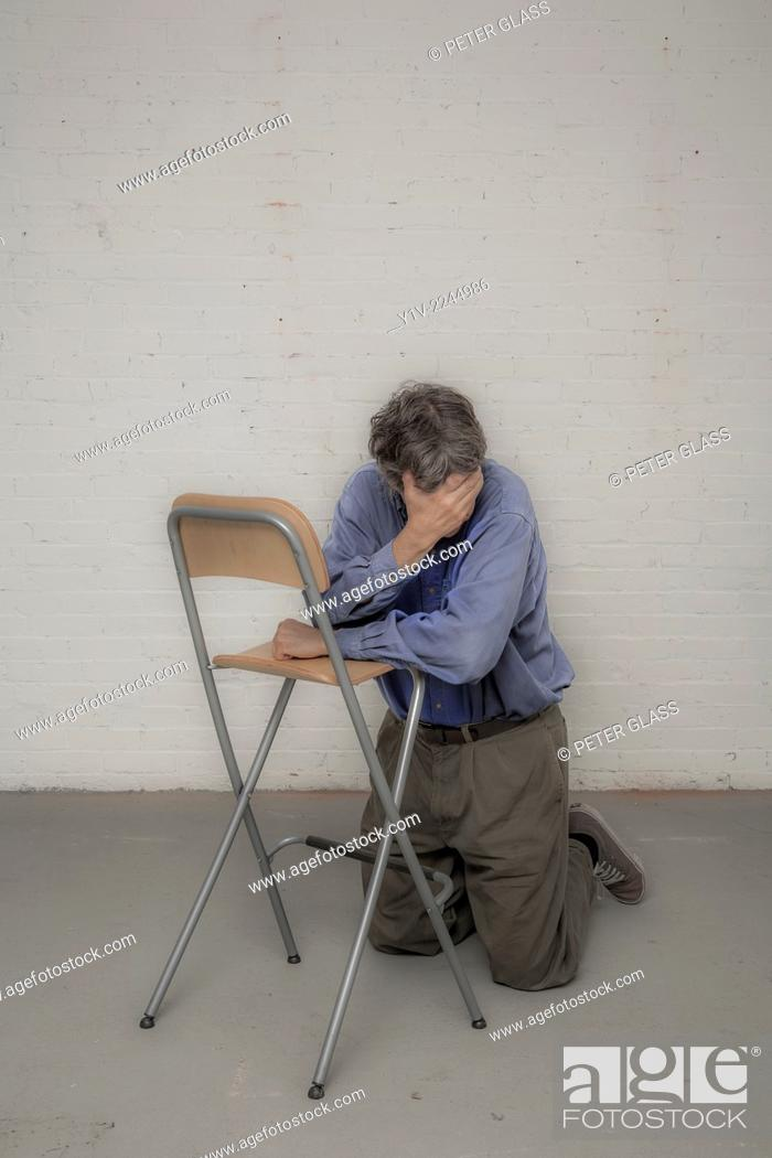 Stock Photo: Man leaning on a chair.