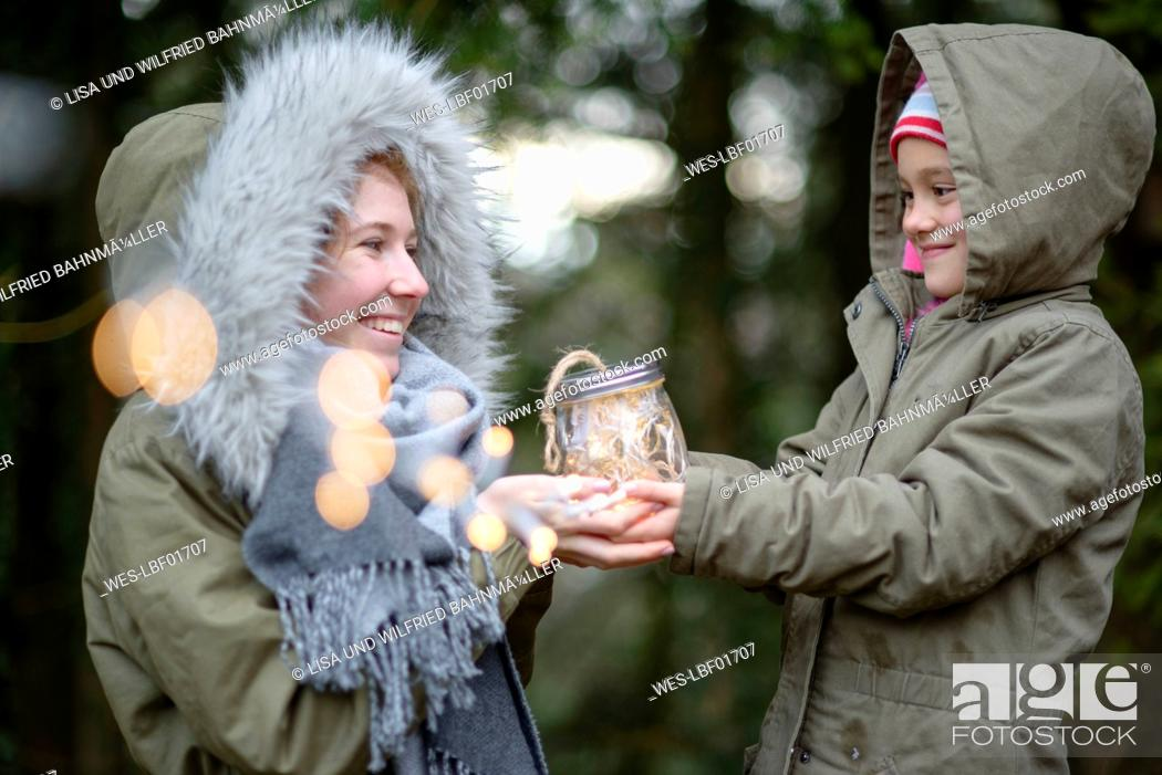 Stock Photo: Little girl surprising her sister with self-made gift outdoors.