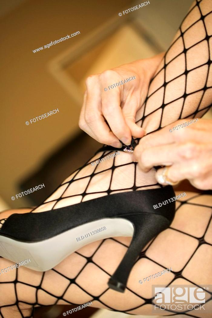 Stock Photo: Close up of woman in fishnet stockings putting on high heel shoes.