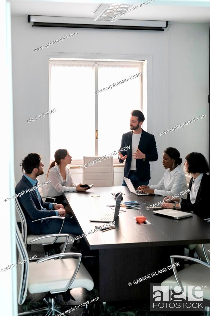 Stock Photo: Young female and male business creative team at conference table presentation.