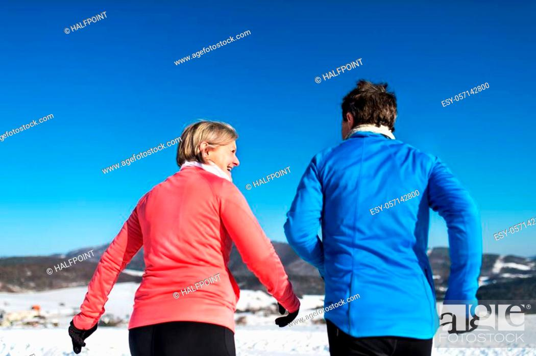 Stock Photo: Rear view of senior couple jogging in snowy winter nature.