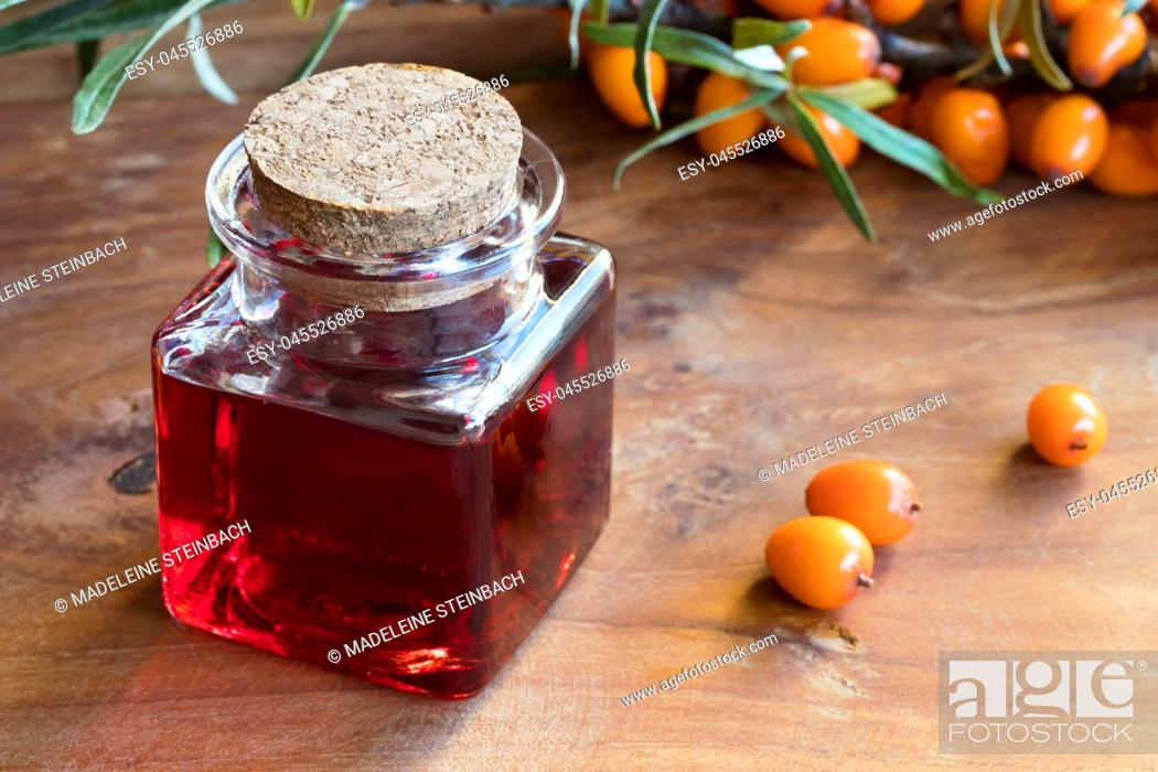Stock Photo: Sea buckthorn oil in a glass jar with sea buckthorn berries and leaves in the background.