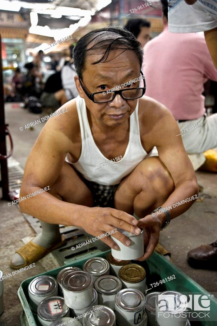 Stock Photo: A man in the pet market looking for a cricket. Shanghai, China.