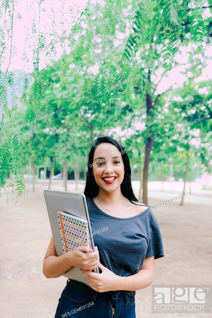 Stock Photo: Smiling young woman holding a laptop and a notebook outdoors.
