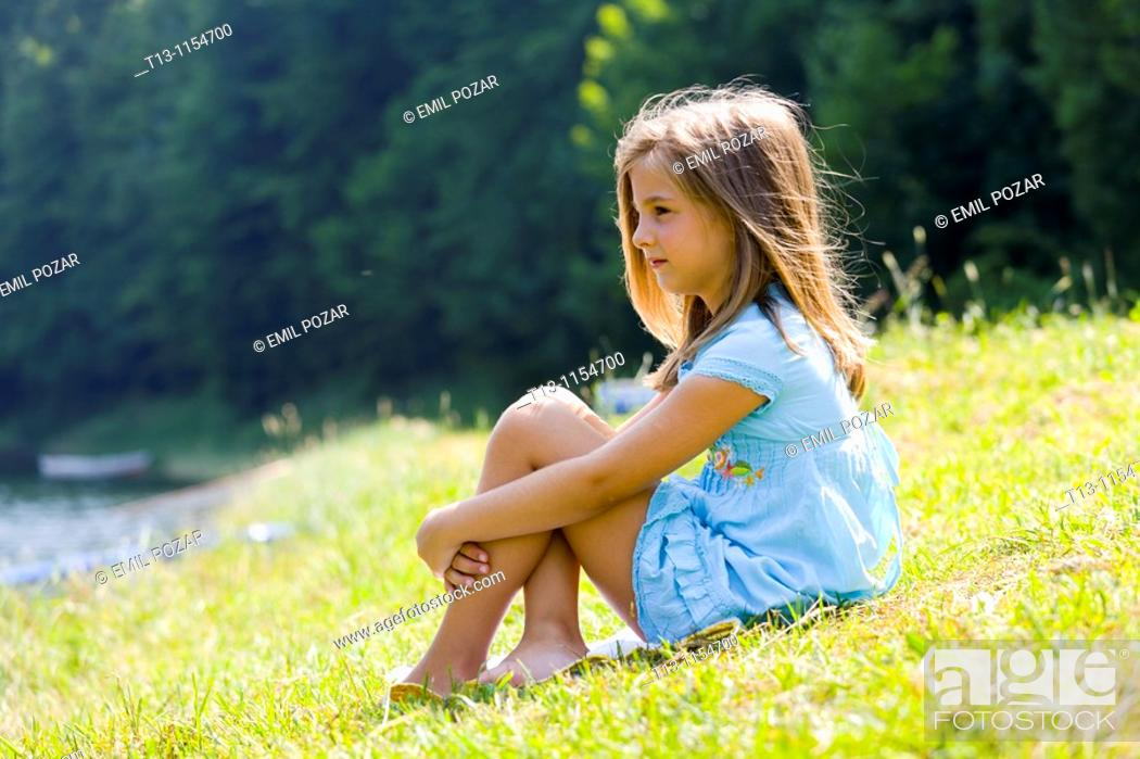 Stock Photo: Six year old girl is sitting on a meadow.