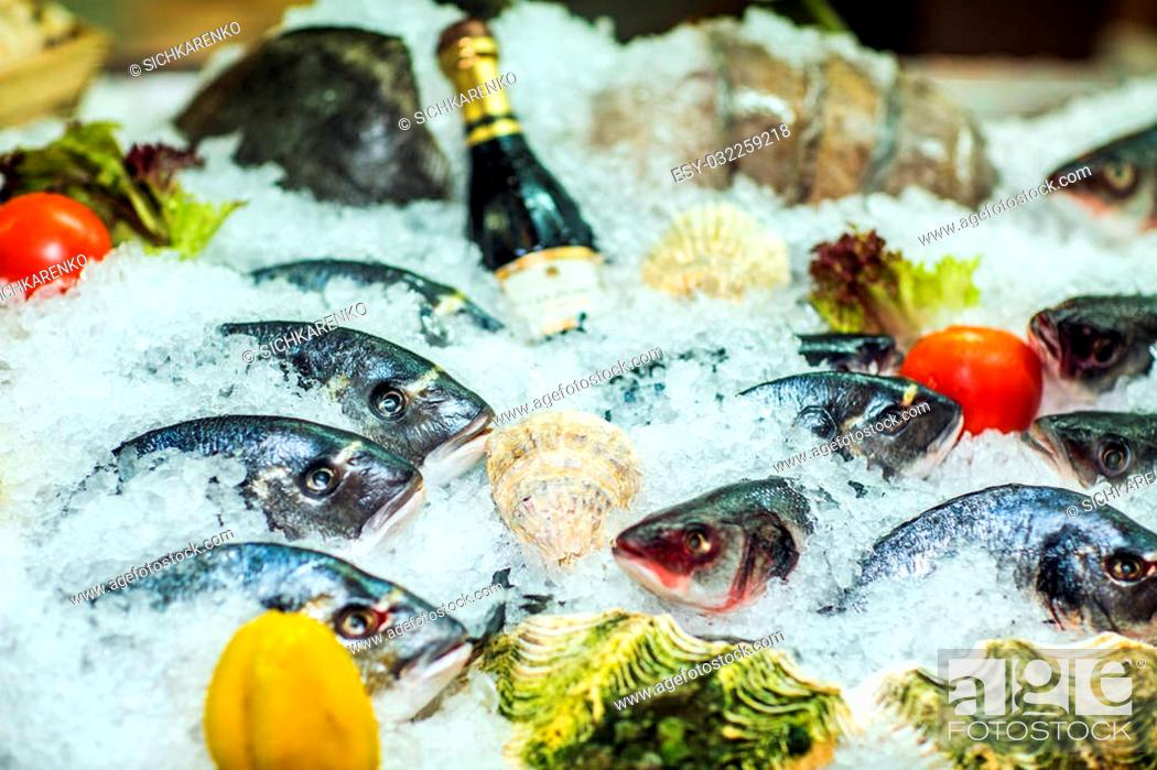 Stock Photo: Different kinds of fish on ice with fresh vegetables. Close-up.