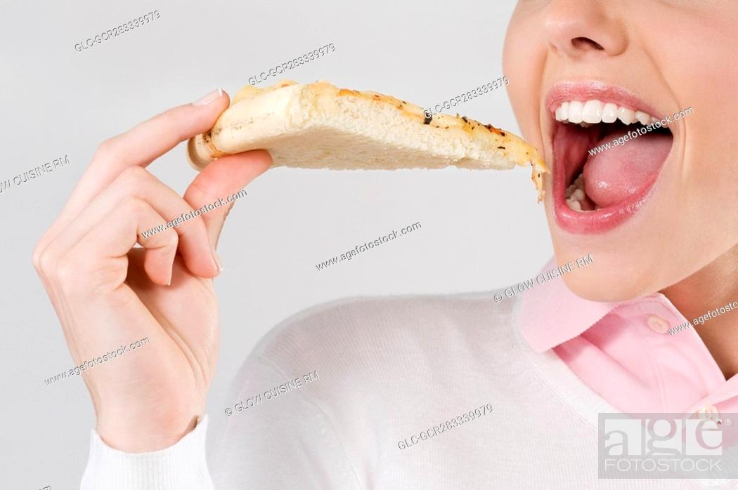 Stock Photo: Female chef eating a slice of pizza.
