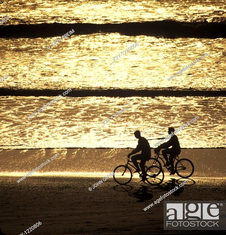 Stock Photo: Silhouette of couple biking along the beach, Cape Cod.