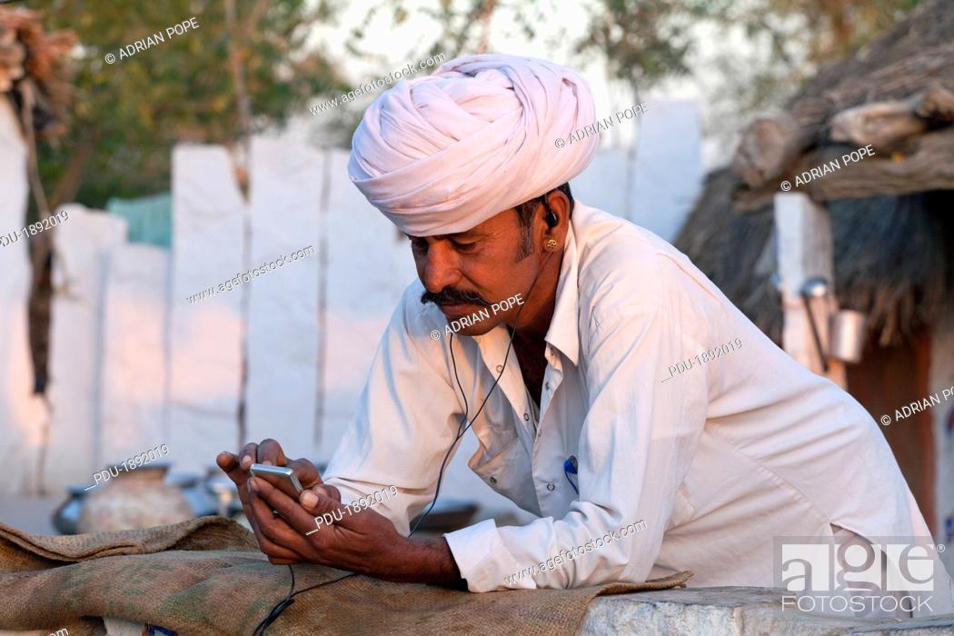 Stock Photo: India, Rajasthan, Jodhpur, Village man listening to mp3 player through headphones.